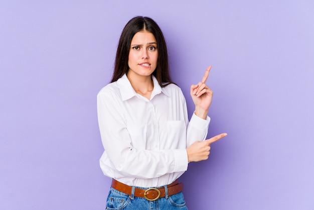 A mulher caucasiano nova na parede roxa chocou apontar com indicadores para um espaço em branco.
