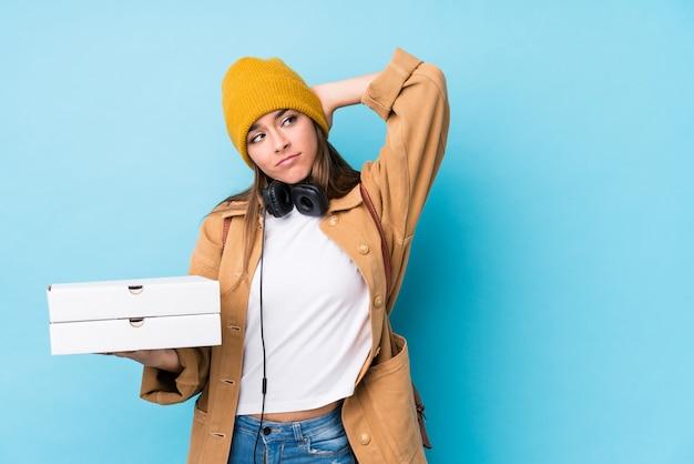 A mulher caucasiano nova que guarda as pizzas isolou-se tocando na parte de trás da cabeça, pensando e fazendo uma escolha.