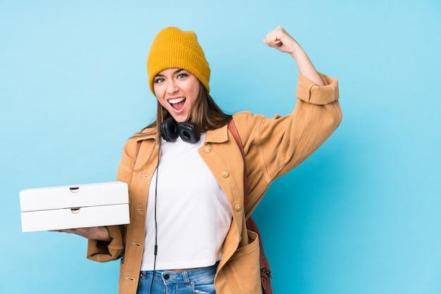A mulher caucasiano nova que guarda pizzas isolou o levantamento do punho após uma vitória, conceito do vencedor.