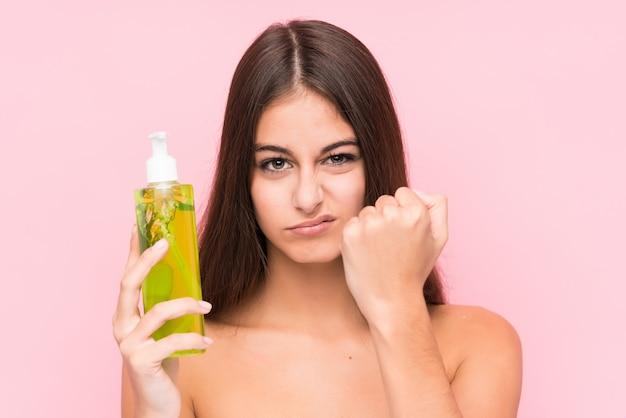 A mulher caucasiano nova que guarda um creme hidratante com aloe vera isolou mostrar o punho com com expressão facial agressiva.