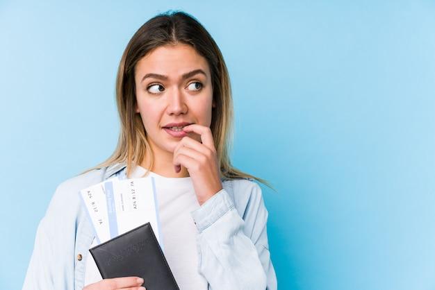 A mulher caucasiano nova que guarda um passaporte isolou o pensamento relaxado sobre algo que olha um espaço da cópia.