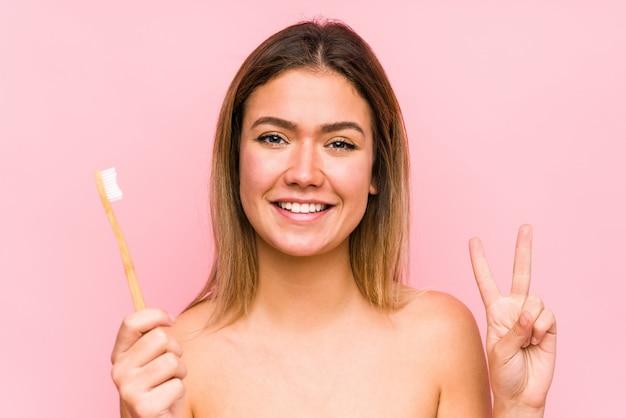 A mulher caucasiano nova que guarda uma escova de dentes isolou mostrar o número dois com dedos.