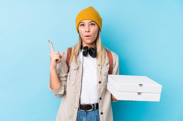 A mulher caucasiano nova que mantem pizzas isolou-se tendo alguma grande ideia, conceito da faculdade criadora.