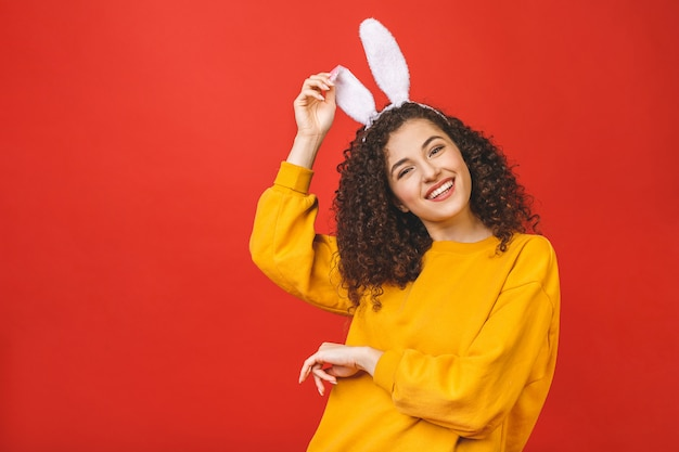 A mulher caucasiano nova que veste as orelhas de coelho bonitos de easter sobre o vermelho isolou o fundo ao sorrir seguro e feliz.