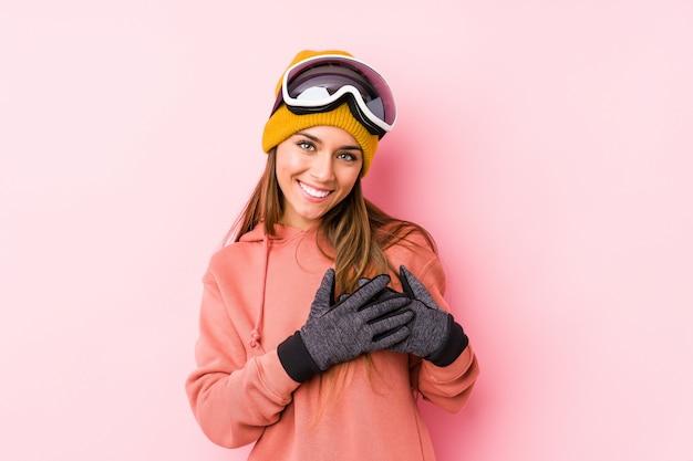 A mulher caucasiano nova que veste um esqui veste o riso isolado mantendo as mãos no coração, conceito da felicidade.