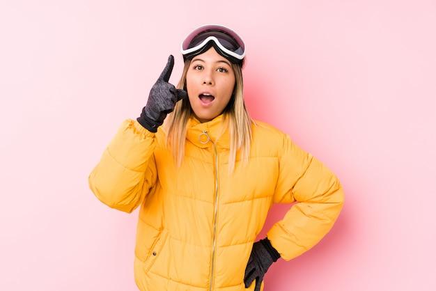 A mulher caucasiano nova que veste um esqui veste-se em uma parede cor-de-rosa que tem uma ideia, conceito da inspiração.