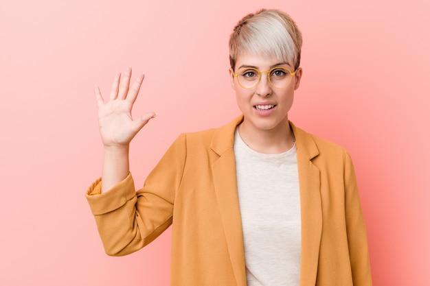 A mulher caucasiano nova que veste um negócio ocasional veste o sorriso que mostra alegre número cinco com dedos.