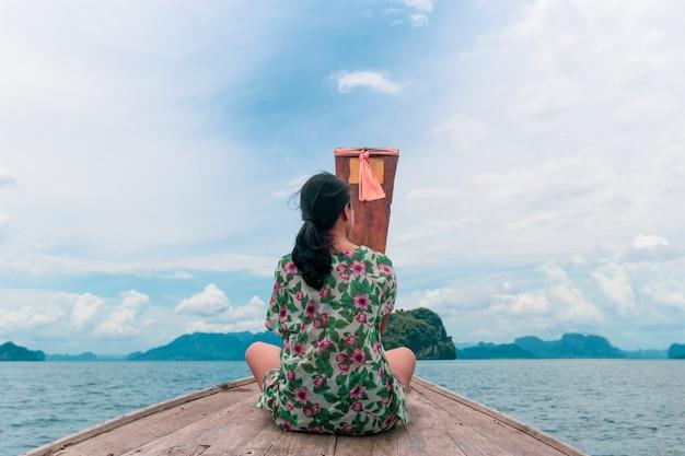 A mulher caucasiano senta-se no barco para fora na opinião traseira do oceano.