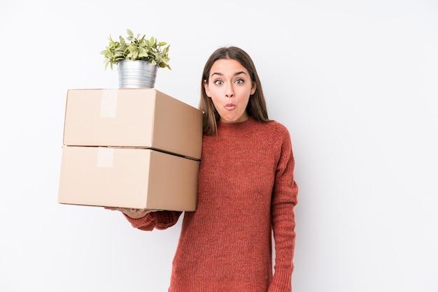 A mulher caucasic nova que guarda caixas isolado encolhe os ombros e abre os olhos confusos.