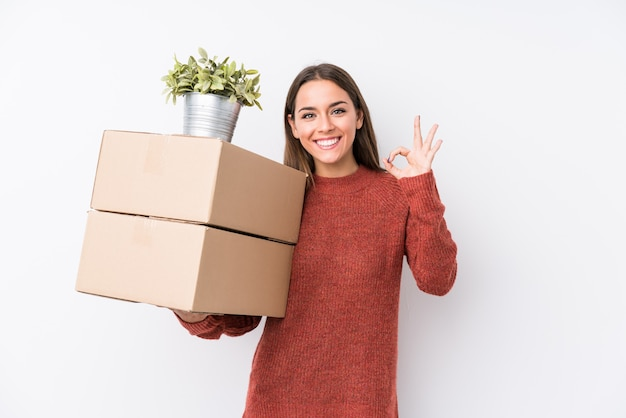 A mulher caucasic nova que guarda caixas isolou alegre e seguro mostrando o gesto aprovado.