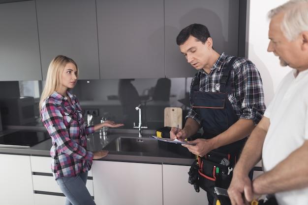 A mulher chamou dois encanadores para consertar a pia da cozinha.