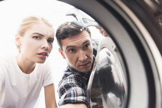 A mulher chamou o reparador para fixar a máquina de lavar.