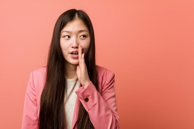A mulher chinesa de negócios jovem vestindo terno rosa está dizendo uma notícia secreta sobre a frenagem quente e olhando de lado