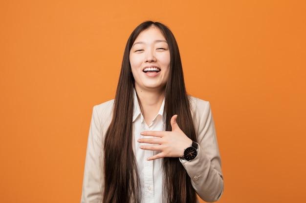 A mulher chinesa do negócio novo ri para fora ruidosamente mantendo a mão na caixa.