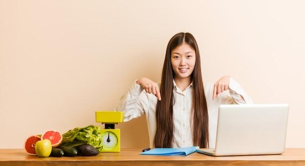 A mulher chinesa do nutricionista novo que trabalha com seu portátil aponta para baixo com os dedos, sentimento positivo.