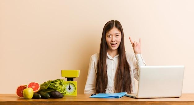 A mulher chinesa do nutricionista novo que trabalha com seu portátil que mostra chifres gesticula como um conceito da revolução.