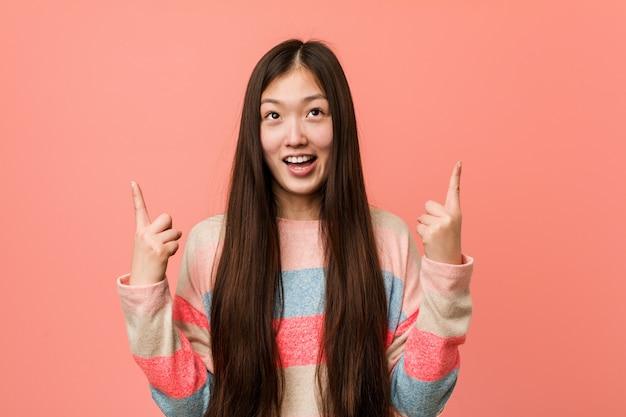 A mulher chinesa fresca nova indica com ambos os dedos dianteiros que mostram acima um espaço vazio.