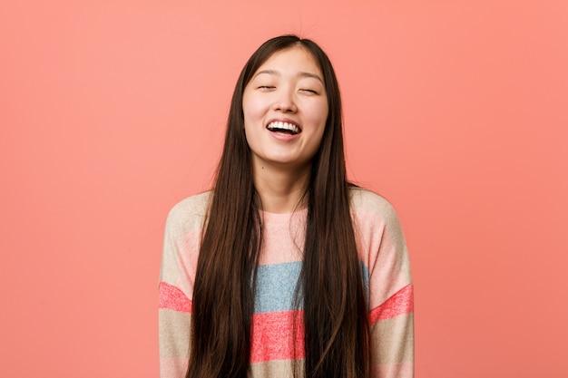A mulher chinesa fresca nova relaxou e o riso feliz, pescoço esticou mostrando os dentes.