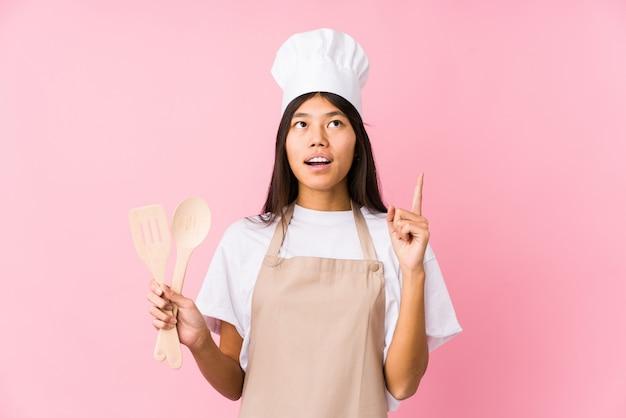A mulher chinesa nova do cozinheiro chefe isolou apontar a cabeça com boca aberta.