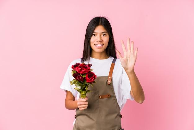 A mulher chinesa nova do jardineiro guardando rosas isolou a exibição alegre de sorriso número cinco com dedos.