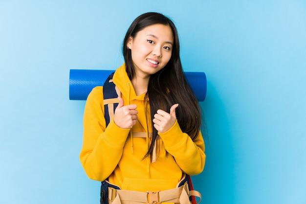 A mulher chinesa nova do mochileiro isolou levantando ambos os polegares acima, sorrindo e seguro.