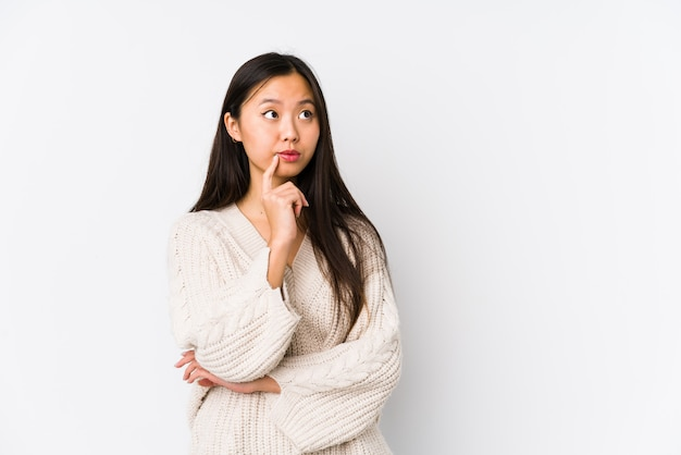 A mulher chinesa nova isolou a vista lateralmente com expressão duvidosa e cética.