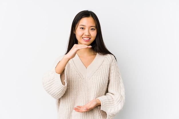 A mulher chinesa nova isolou guardar algo com ambas as mãos, apresentação do produto.