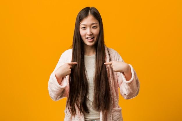 A mulher chinesa nova no pyjama surpreendeu apontar nsi mesmo, sorrindo amplamente.
