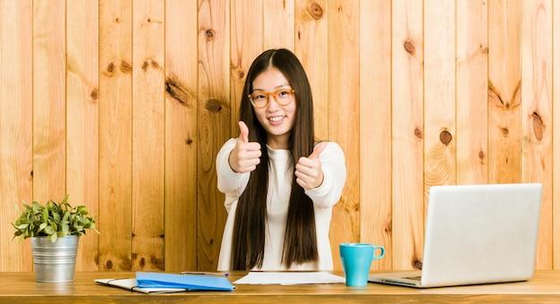 A mulher chinesa nova que estuda em sua mesa com polegares levanta, elogios sobre algo, apoia e respeita o conceito.