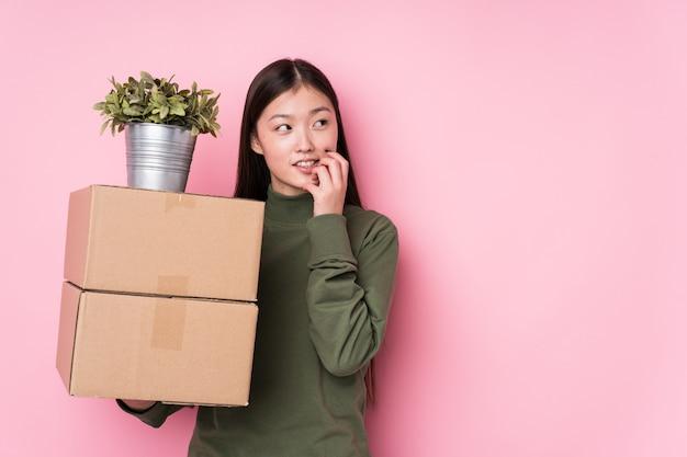 A mulher chinesa nova que guarda caixas relaxou o pensamento sobre algo que olha um espaço em branco.