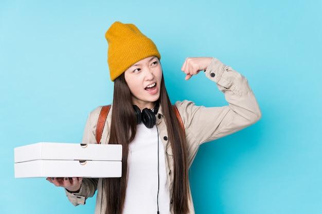 A mulher chinesa nova que guarda pizzas isolou o levantamento do punho após uma vitória, conceito do vencedor.