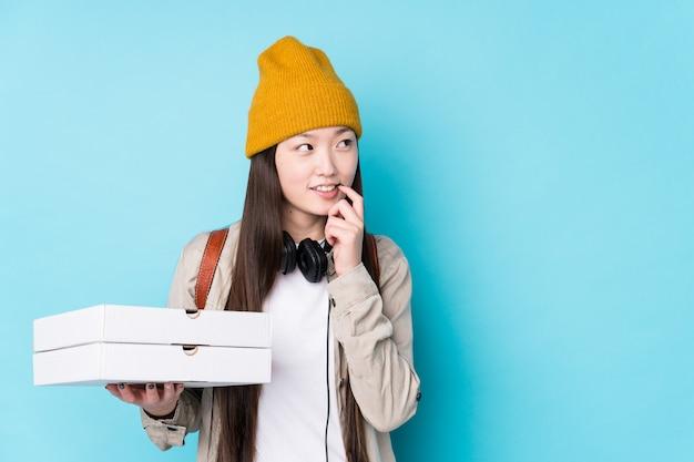 A mulher chinesa nova que guarda pizzas isolou o pensamento relaxado sobre algo que olha um espaço da cópia.