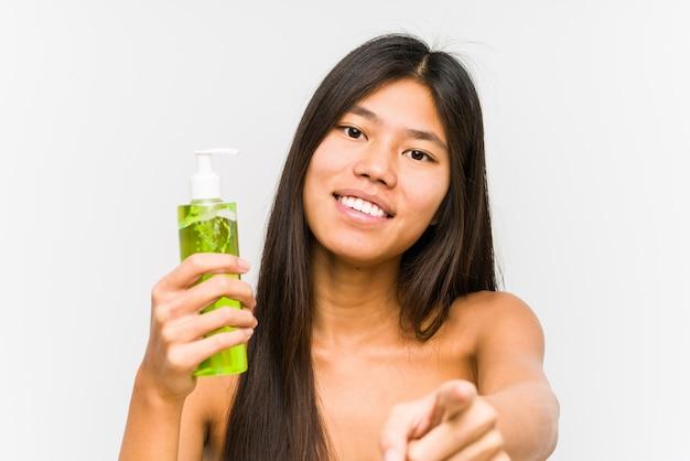 A mulher chinesa nova que guarda um creme hidratante com aloés vera isolou os sorrisos alegres que apontam para a parte dianteira.