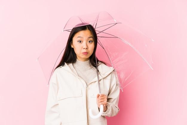 A mulher chinesa nova que guarda um guarda-chuva isolado encolhe os ombros e abre os olhos confusos.