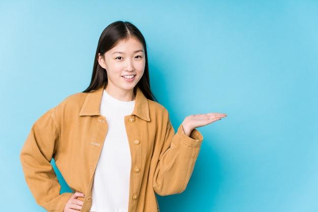A mulher chinesa nova que levanta em uma parede azul isolou mostrar um espaço da cópia em uma palma e guardar outra mão na cintura.