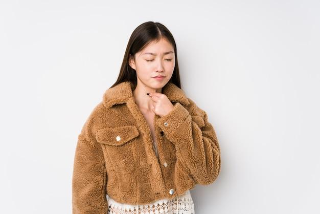A mulher chinesa nova que levanta em uma parede branca isolada sofre a dor na garganta devido a um vírus ou uma infecção.