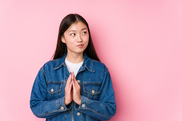 A mulher chinesa nova que levanta em uma parede cor-de-rosa isolou a composição do plano na mente, estabelecendo uma ideia.
