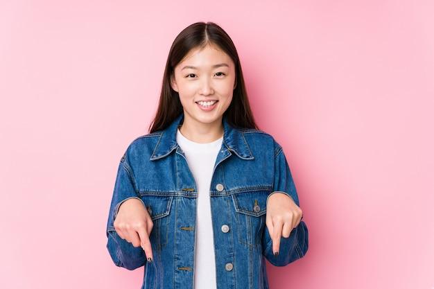 A mulher chinesa nova que levanta em uma parede cor-de-rosa isolou pontos para baixo com dedos, sentimento positivo.