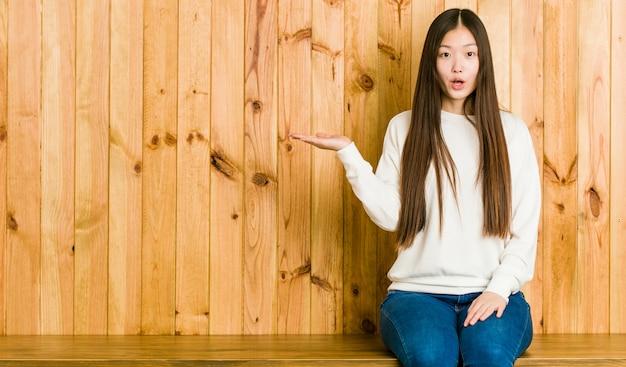 A mulher chinesa nova que senta-se em um lugar de madeira imprimiu guardar o espaço da cópia na palma.