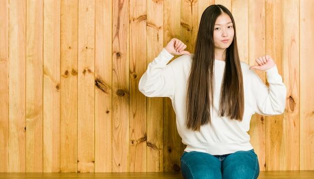 A mulher chinesa nova que senta-se em um lugar de madeira sente orgulhosa e auto-confiante, exemplo a seguir.