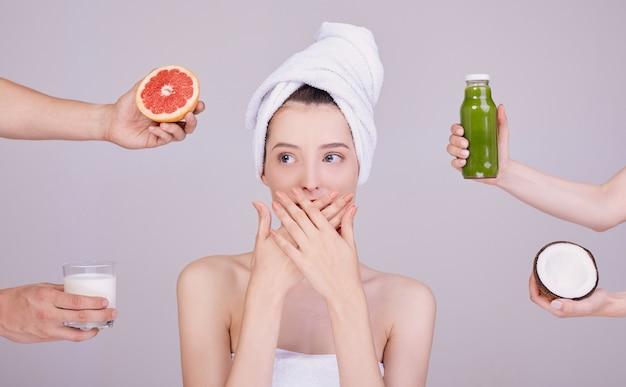 A mulher cobre a boca com a mão, em torno da mão com alimentos e bebidas.