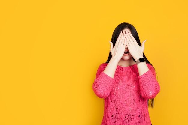 A mulher cobriu os olhos com as mãos e abriu a boca, contra uma parede amarela, com espaço para texto. conceito de emoções de choque, expectativa, surpresa