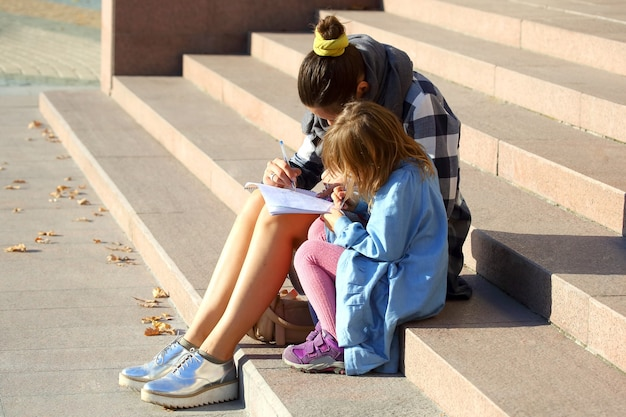 A mulher com a menina desenhando em um caderno enquanto está sentada na escada