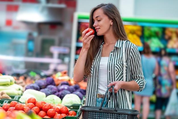 A mulher com cesto de compras escolhe tomates vermelhos orgânicos frescos no departamento vegetal do supermercado. cliente que compra comida na mercearia