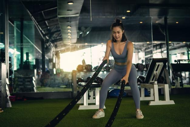 A mulher com cordas da batalha da corda da batalha exercita no gym da aptidão.
