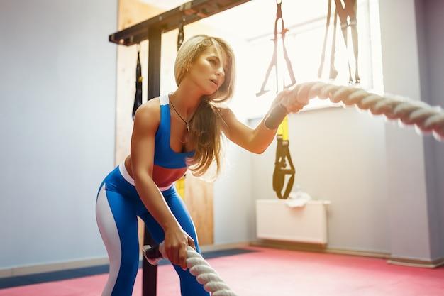 A mulher com cordas de batalha exercita-se no ginásio da aptidão. jovem fêmea vestindo roupas esportivas.
