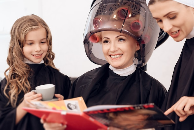A mulher com encrespadores de cabelo seca o cabelo junto com a filha.