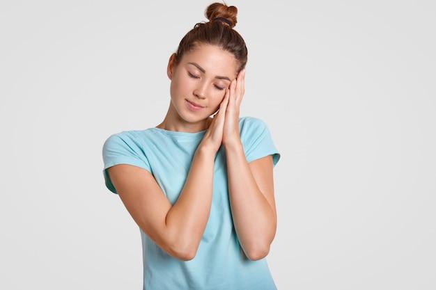 A mulher com sono se inclina para as duas mãos, mantém os olhos fechados, vestido com roupas casuais, quer descansar depois da noite sem dormir, posa sozinha contra a parede branca. conceito de pessoas, cansaço e sonhos