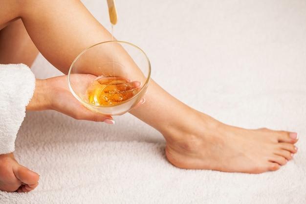 A mulher com uma pele perfeita nas pernas aplicou cera para remover pêlos
