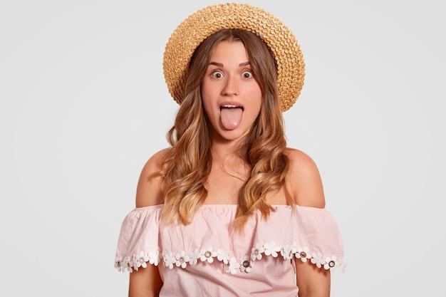 A mulher cômica bonita engraçada mostra a língua